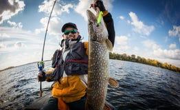 Pescatore e grande luccio del trofeo fotografie stock