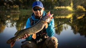 Pescatore e grande luccio del trofeo fotografia stock