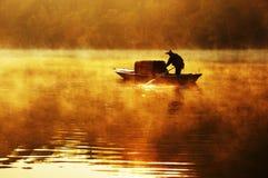 Pescatore e la sua barca in una mattina nebbiosa con luce solare dorata Immagini Stock
