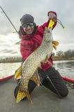 Pescatore felice con il grande trofeo del pesce del luccio alla barca con le attrezzature di pesca immagine stock