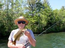 Pescatore Holding Bass With un lago ed alberi nei precedenti immagine stock libera da diritti