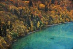 Pescatore irriconoscibile in una barca su un lago e su una foresta autunnale sulla Banca Foto con i colori evidenziati stessi immagini stock