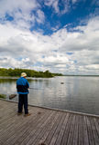 Pescatore maggiore su un pilastro fotografia stock libera da diritti
