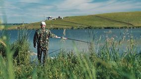 Pescatore nei fermi dei vestiti del cammuffamento video d archivio