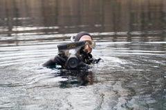 Pescatore nella macchina fotografica della tenuta della muta umida in scatola impermeabile fotografie stock libere da diritti