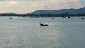 Pescatore non identificabile vago con il suo peschereccio che attraversa l'oceano blu davanti alle montagne nei precedenti stock footage