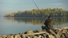 Pescatore professionista che pesca sulla sponda del fiume, sul primo piano del galleggiante, sulla barretta e sull'attrezzatura stock footage