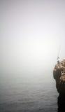 Pescatore in scogliera Fotografia Stock