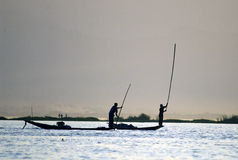 Pescatore Silhouettes al tramonto. Immagine Stock