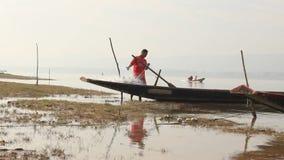Pescatore solo laotiano che pulisce e che controlla le sue reti da pesca sulle banche del Mekong archivi video