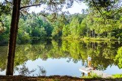 Pescatore Standing sul pilastro nel bello lago Immagini Stock Libere da Diritti