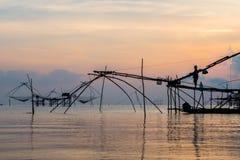 Pescatore su macchinario di bambù di mattina Immagine Stock