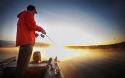 Pescatore su un lago di tramonto fotografie stock