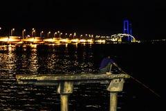 Pescatore su un pesce concreto del fermo del pilone alla notte In ponte di Suramadu del backround a penombra, Soerabaya, Indonesi immagini stock