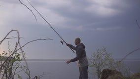 Pescatore su un viaggio di pesca su un lago con una canna da pesca in sua mano archivi video