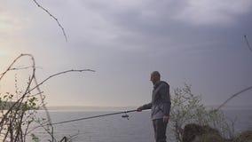 Pescatore su un viaggio di pesca su un lago con una canna da pesca in sua mano stock footage