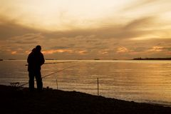 Pescatore su una costa di mare e tramonto maestoso sopra acqua Immagine Stock Libera da Diritti