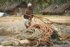 Pescatore su una spiaggia che raccoglie le corde Immagine Stock