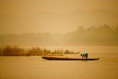 Pescatore sul fiume al tramonto Immagine Stock