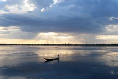 Pescatore sulla barca con il tramonto fotografia stock libera da diritti