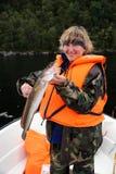 Pescatore sulla barca in maglia arancione con la sua cattura. Fotografie Stock Libere da Diritti