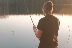 Pescatore sullo stagno Il giovane tipo con teme in vetri in un pesce di pesca della maglietta con la barretta Fotografia Stock