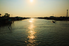 Pescatore in una barca con il tramonto alla Tailandia Fotografia Stock