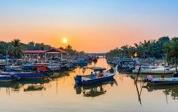 Pescatori che escono al mare in barca durante il tramonto fotografia stock libera da diritti