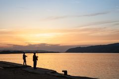 Pescatori che pescano sulla banchina di Veliko Gradiste al tramonto sul Danubio Fotografie Stock