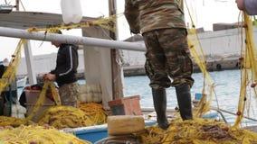 Pescatori che puliscono le reti su una barca archivi video