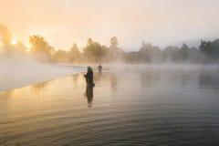 Pescatori che tengono canna da pesca, stante nel fiume fotografia stock libera da diritti