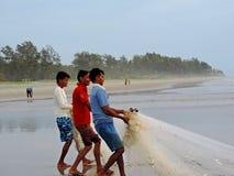 Pescatori che tirano la rete con il banco di pesci Immagini Stock