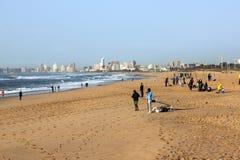 Pescatori di mattina sulla spiaggia con l'orizzonte di Durban nel fondo Immagine Stock