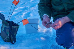 Pescatori impegnati nella pesca sul ghiaccio Immagini Stock