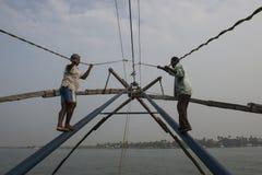 Pescatori indù che selezionano una rete cinese Il Kochi forte, India Fotografia Stock