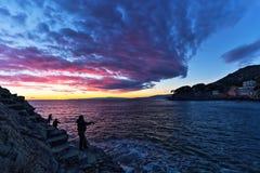 Pescatori sotto un bello cielo dopo il tramonto, Italia immagini stock libere da diritti