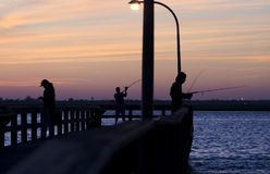 Pescatori su Pier At Twilight Fotografie Stock
