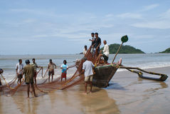 Pescatori sulla spiaggia di Palolem e sulla barca di legno Immagini Stock