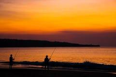 Pescatori sulla spiaggia sull'isola di Bali al tramonto fotografia stock