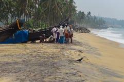 Pescatori vicino alla barca sulla spiaggia in Kovalam Fotografia Stock