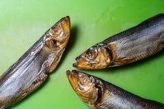 Pesce affumicato dello spratto tre su un tagliere verde fotografia stock libera da diritti
