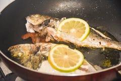 Pesce al forno fritto fresco con le scaglie e limone in una padella Immagine Stock