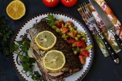 Pesce al forno su un piatto con il limone, l'insalata ed i verdi immagine stock libera da diritti