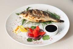 Pesce arrostito con il pomodoro, le erbe, le cipolle ed il limone Immagine Stock