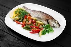 Pesce arrostito con le verdure sul piatto bianco Fotografia Stock