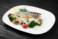 Pesce arrostito con le verdure sul piatto bianco Immagini Stock