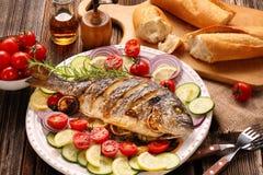 Pesce arrostito di dorada con le verdure su fondo di legno immagine stock