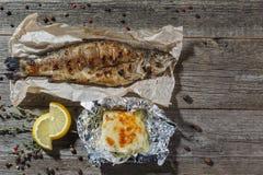 Pesce arrostito di dorado con i cavolini di Bruxelles del limone, pomodori, garli Immagine Stock