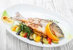 Pesce arrostito di dorado con le verdure al forno ed i rosmarini sul piatto sulla fine di legno del fondo su immagine stock libera da diritti