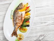 Pesce arrostito di dorado con le verdure al forno ed i rosmarini sul piatto sulla fine di legno del fondo su immagine stock